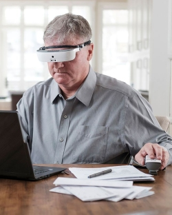 Man using head mounted magnifier